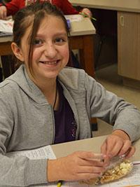 Sixth-grade student Layna Richards-Raymond eats popcorn trail mix
