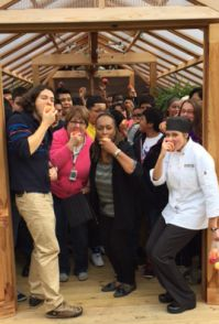 Teachers, administrators and students gather inside the new greenhouse to bite apple at the same time
