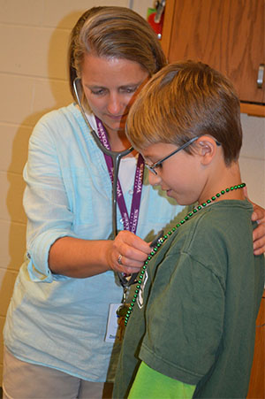 Amy Loftis-Tuitel, Wyoming Public Schools' new health care specialist listens to a student's lungs