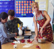 Students Miriam Vargas and Gerry Johnson mix cake with teacher Katy Andreini