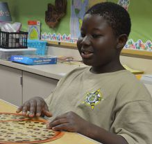 Jerreh Saidykhan learns fractions with pizza slices
