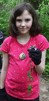 Fifth-grade student Allison Moore holds a flower while exploring the woods at Hagar Park