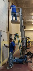 Grand Rapids First Church volunteers Jeff Jirinec and Larry Hollemans spruce up the Wyoming High School wrestling room