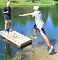 Students James Daniels takes a leap while Drake Poulson watches
