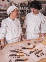 Sarah Waller and her student add the final touches to a batch of biscotti