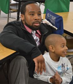 Leontae Couch sits with his son, Jayden, to start his kindergarten school day