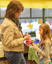 Camp Blodgett Program Director Susan Doughty shows Pine Island Elementary fourth grade student Jadelyn Hall how to make a bracelet