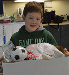 Second grade students Levi Green, who is going to Rwanda with his family, holds toys donated by classmates for African children