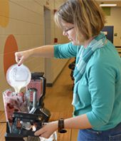 Stoney Creek Elementary School parent Tracy Slack helps mix a smoothie recipe