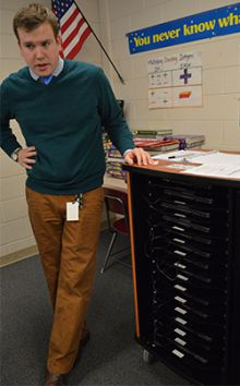 Middle School teacher Brett Lynch stands by a cart of laptops