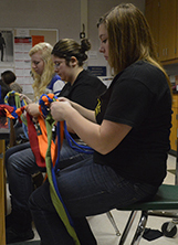 Marissa Delooff creates a dog toy for an animal shelter from old T-shirts students donated