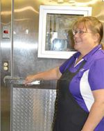 Caledonia Community Schools found money could be saved in the summer by turning off some of its buildings' freezers, like this one Caledonia Elementary lead cook Joyce Zahl enters