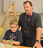 A sixth-grade student works on his mask while art teacher Shawn Dejonge leads class