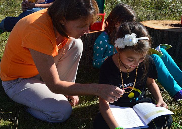 Teacher Pam Bird reads with second grader Zoey Pallick