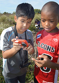 From left, Ja'shawn Huges and Efrain Carranza look at a grasshopper