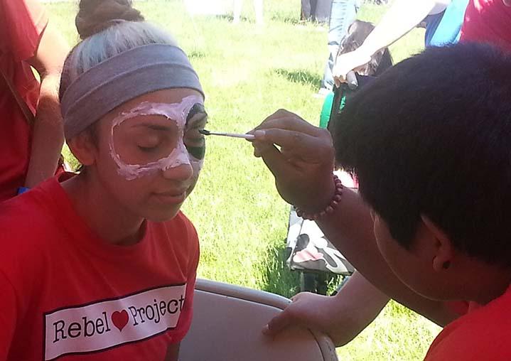 Student David Gutierrez paints student Amelia Navarrete's face