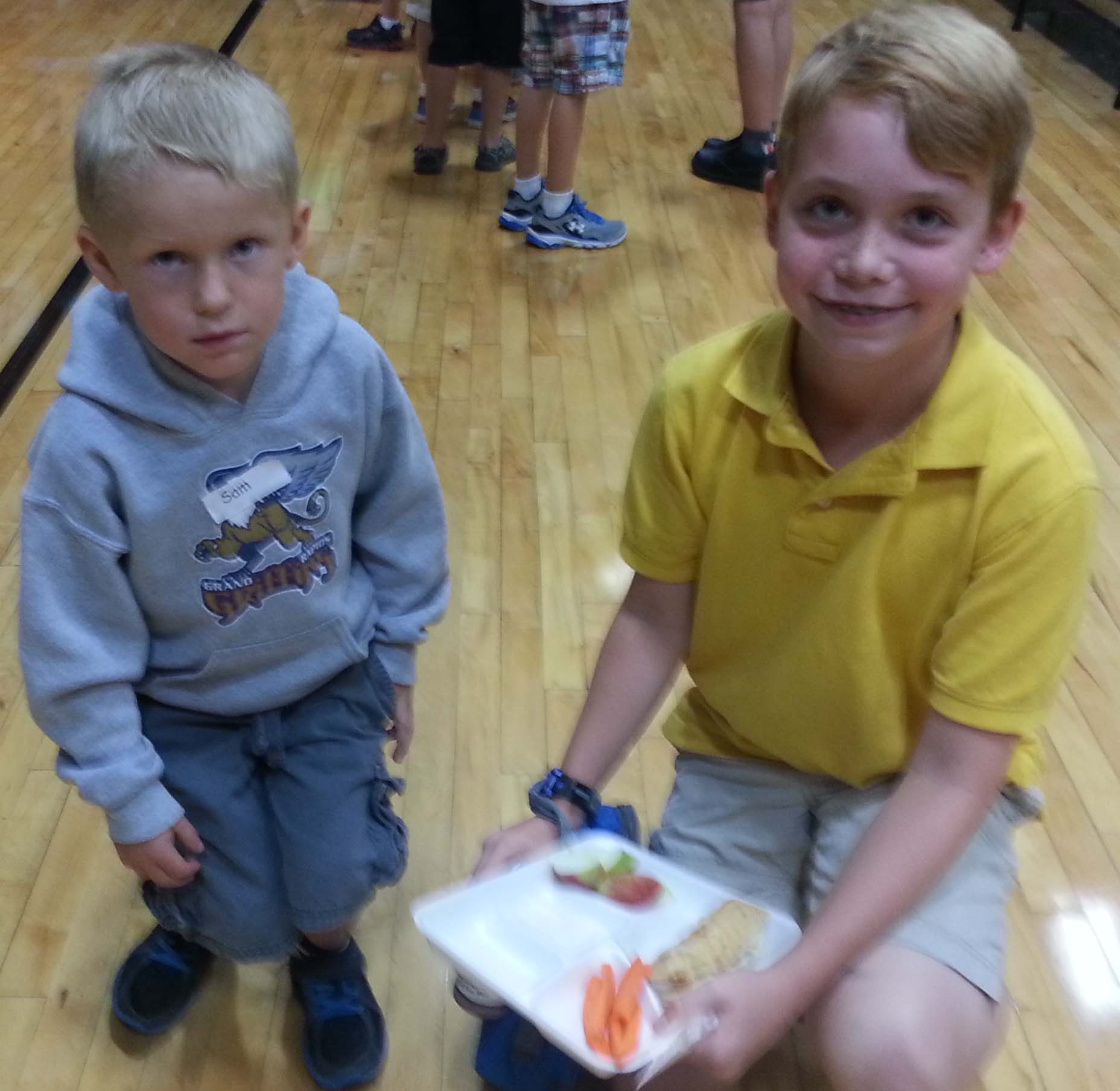 Fifth-grade Ben Blanchard helps Sam Brundin with his lunch tray