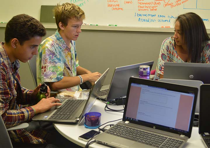 Innovation High students Benjamin Wieringa, Eli Michael and Airyonna Carter discuss a project with a variety of resources available for their use