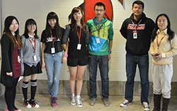 From left, teacher Shelly Ye, students Krystal Liu, Jean Wu, Victoria Xu, Harry Liu, Bill Liu and teacher Jean Wu stand in front of an East Kentwood Falcon