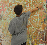 Sixth grader Enrique Domeier stretches for a broad paint stroke