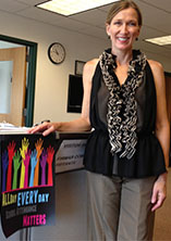 "Godfrey-Lee Psychologist Gina Kuyers stands next to posters for ""All Day Everyday,"" a public campaign that seeks to reduce absenteeism among students in the Early Childhood Center"