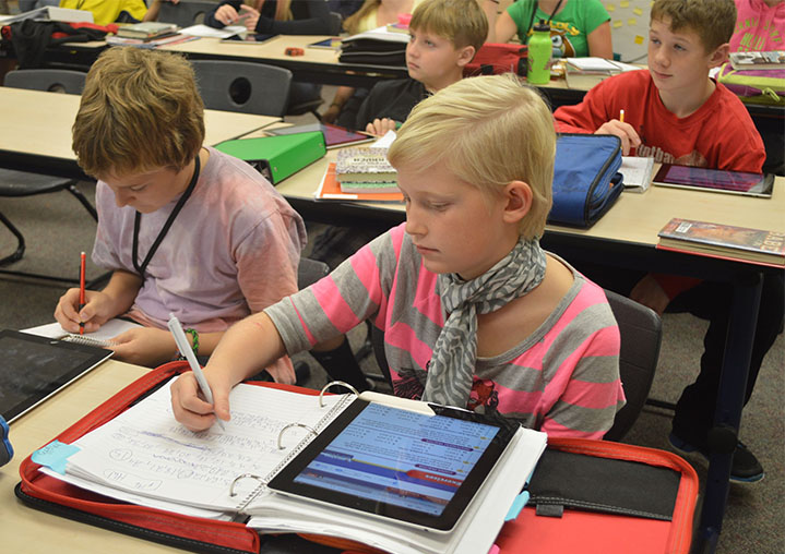 Nickels Intermediate School sixth graders work on math with traditional paper and pencils and iPads