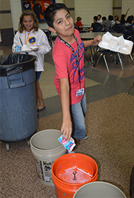 Diego Alvarez dumps waste to recycle his milk carton as part of the Kelloggsville Middle School recycling program, an example of a service-learning project