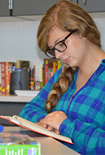Freshman Sophia Rhodes pores over one of the more than 1,000 books in Tilley's classroom library