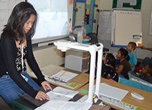 Janet Vu reads a story to second graders as they watch the illustrations on the projector