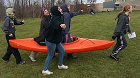 Students carry a canoe at the foraging station