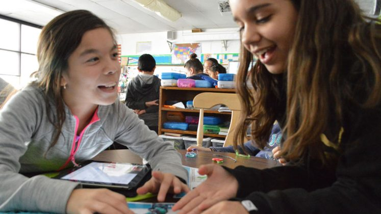 Fourth-graders Isabela Deleon-Magana, left, and Arianna Escribano work on their pictogram