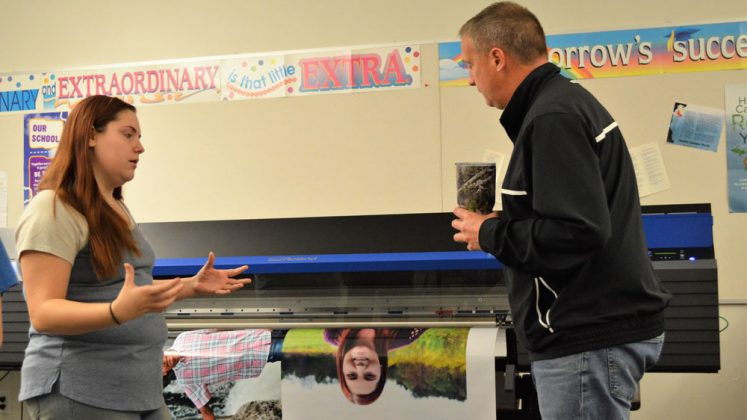 Teacher Ted Smith stops in to discuss the printing progress with senior Melissa Bare