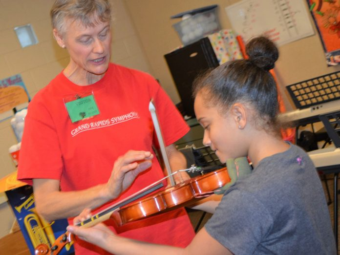 Linda Nelson, violinist with the Grand Rapids Symphony, shows Meeah Fisher how to hold a bow