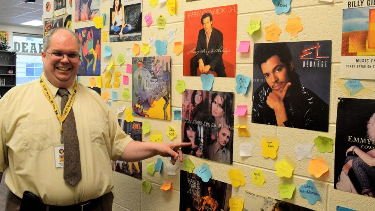 David Lyons proudly displays part of his album-cover wall art, arranged in honor of his 25th year of teaching