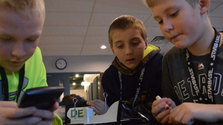 Working with a budget, fifth-graders (from left) Ethan Teachout, Spencer Ybema and Connor Dombkowski calculated the cost of the materials they needed to protect their egg-astronaut