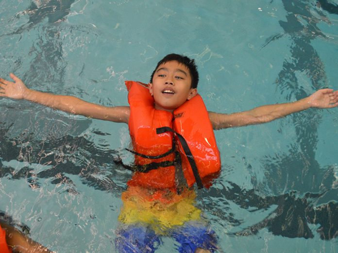 Fifth-grader Jaden Nguyen floats on his back, a water safety skill