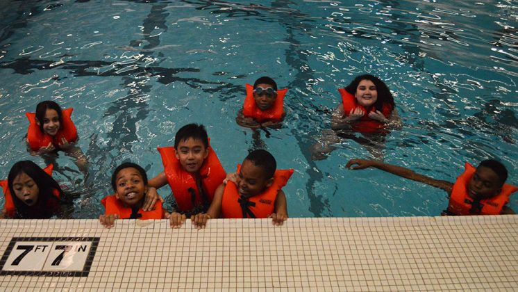 Students practice swimming in deep water