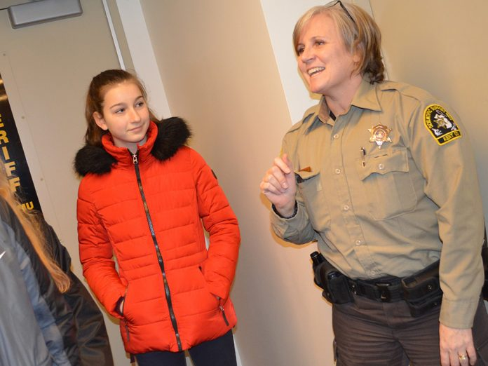 Kent County Sheriff's Department forensic technician Dawn TenBrink shows students from Forest Hills, Lowell, East Kentwood and Wyoming around a simulated crime scene