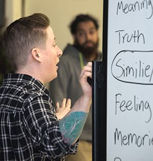 The Diatribe's Rachel Gleason writes poetry ideas on the board, which students learned in the workshop at Valleywood Middle School