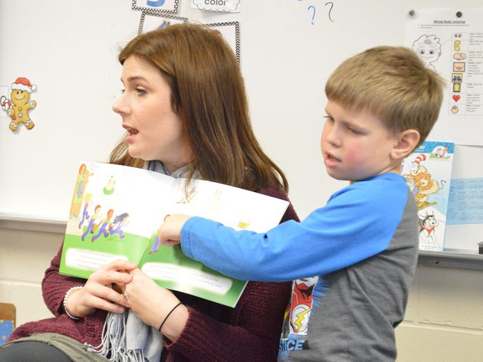 Katee Aubil, speech language pathologist, reads a book about anxiety as part of Social Thinking, with a little help from kindergartner Drake VanLente