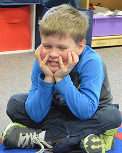 "Emmons Lake kindergarten student Drake VanLente demonstrates ""not following the group plan"" by staying seated while his classmates return to their desks"