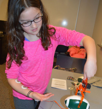 Abigail Bardill, a fourth-grader at Forest Hills Knapp Forest Elementary, watches how command signals from the brain can make a robotic limb move