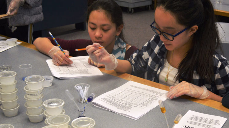 Using glucose test strips, Thoovi Nguyen of Kentwood's Crestwood Middle School, left, and Hannah Ngo from Walker Charter Academy learned iodine turns to a blue-black color if there is starch in a food