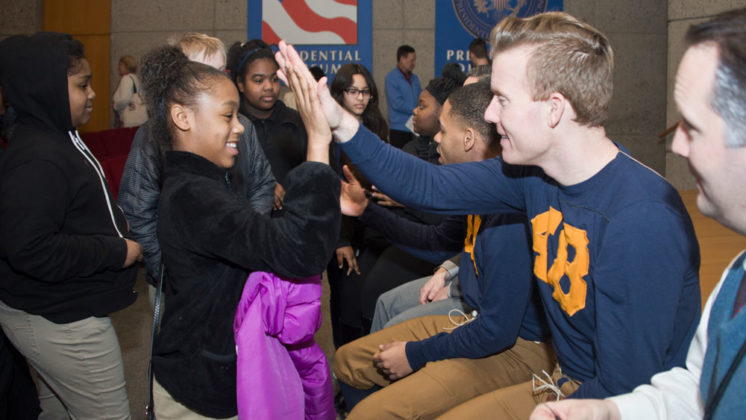 "Jayla Greer, sixth grade, gives a ""high five"" to actor Jesse Aukeman as Gerald Ford. ""My family is made up of white and black and Indian. You can see how people can come together"" after seeing this play. She said she liked it. ""It taught me more about the history. I like the actors. They're cool. They are all good actors and represent good people."""