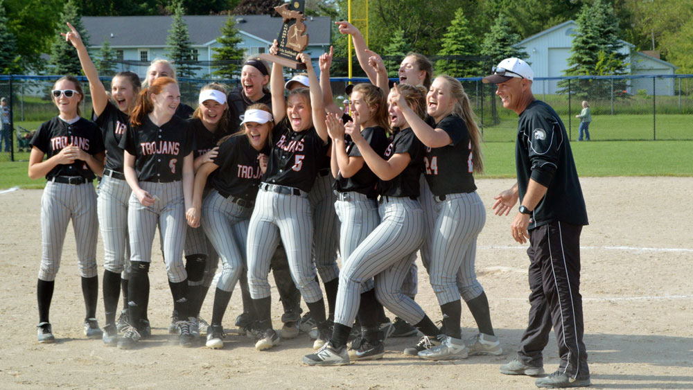 Thornapple Kellogg softball team celebrates its Division 2 district championship win over Wayland on June 3 in Hopkins