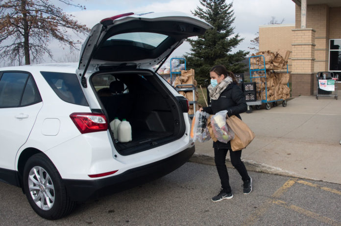 Melissa Lemaire, a high school food service worker, loads up a car with several bags of food